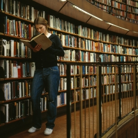 A woman reads a book in a library.