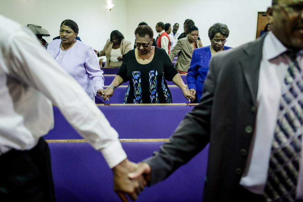 A Baptist community holds hands during church.