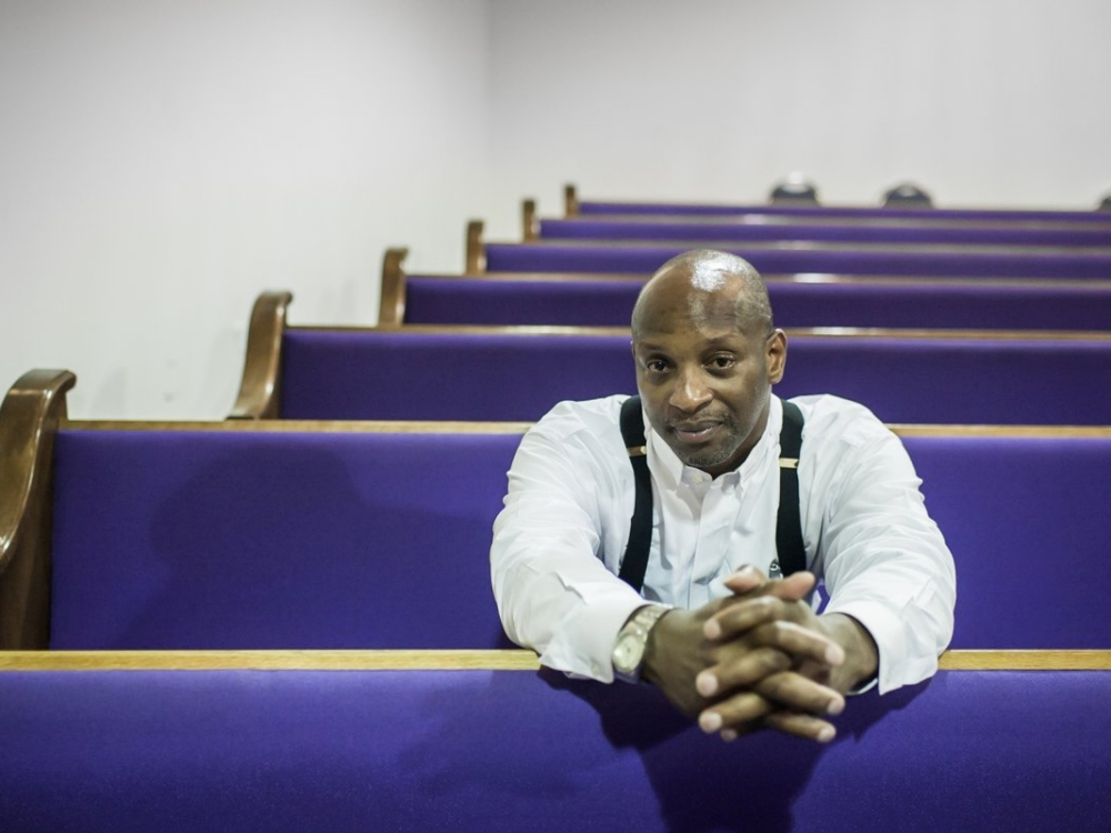 A pastor sits in a pew at his church.