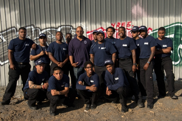EMS Corps training graduates pose in front of a wall of graffiti.