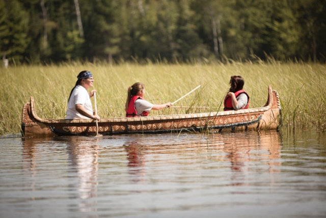 A family uses a canoe to harvest wild rice.