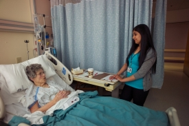 A senior nursing student assists a hospital patient.