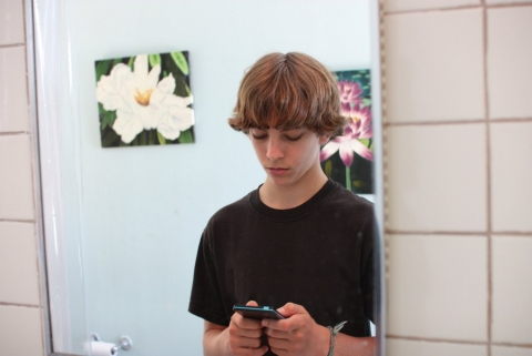 Reflection of a boy in a bathroom mirror. He is typing on a cell phone