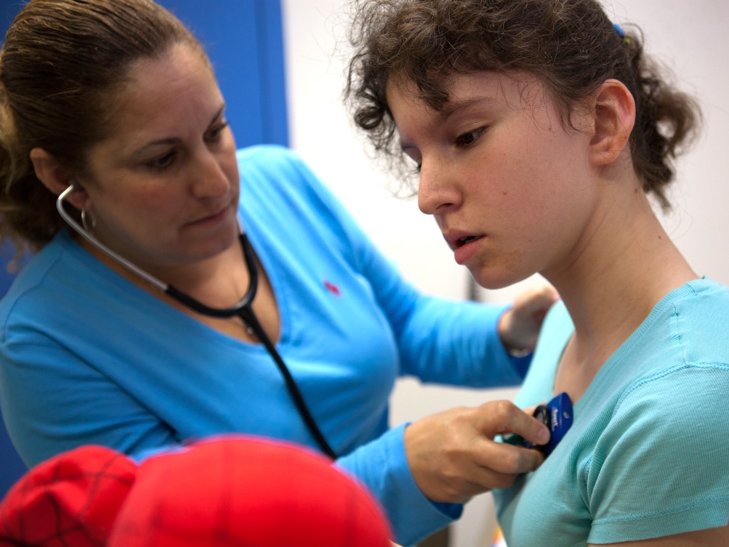 A medical professional listens to a girl's heart using a stethoscope.