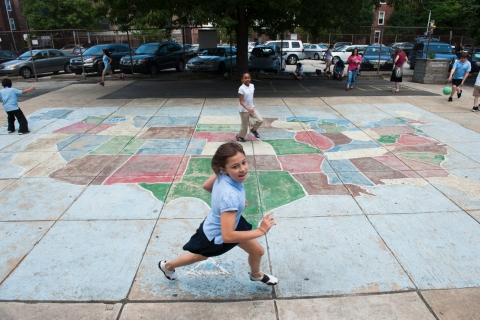 Girl running outside near a chalk drawing of the continental United States.