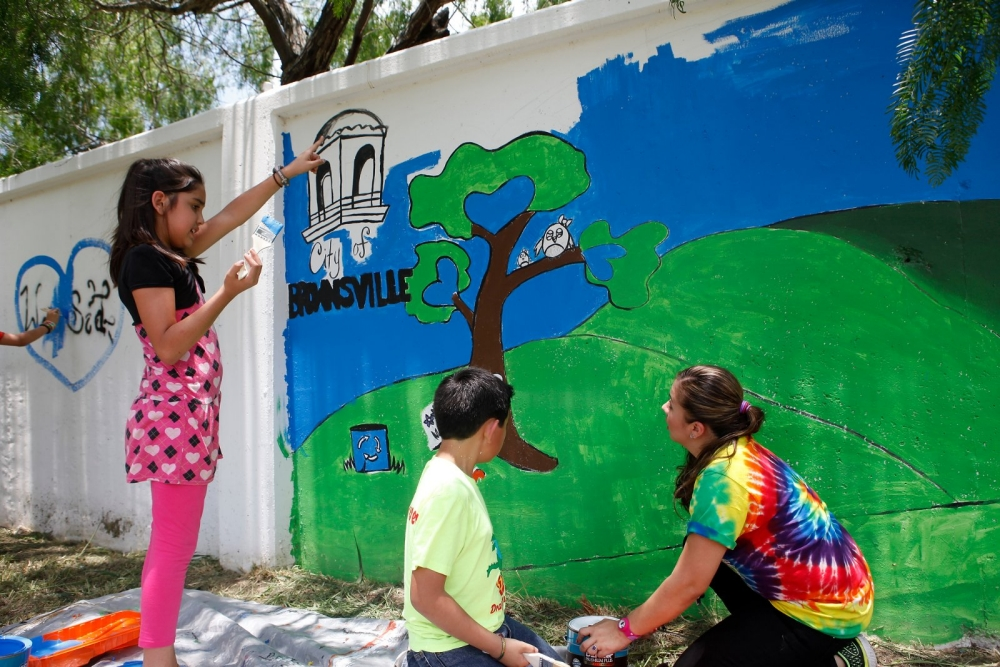 Art teacher Fatima Lai and her students paint a mural at Skinner Elementary School in Brownsville, Texas.