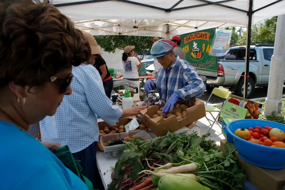 Customer buys produce at the Brownsville Farmers' Market.