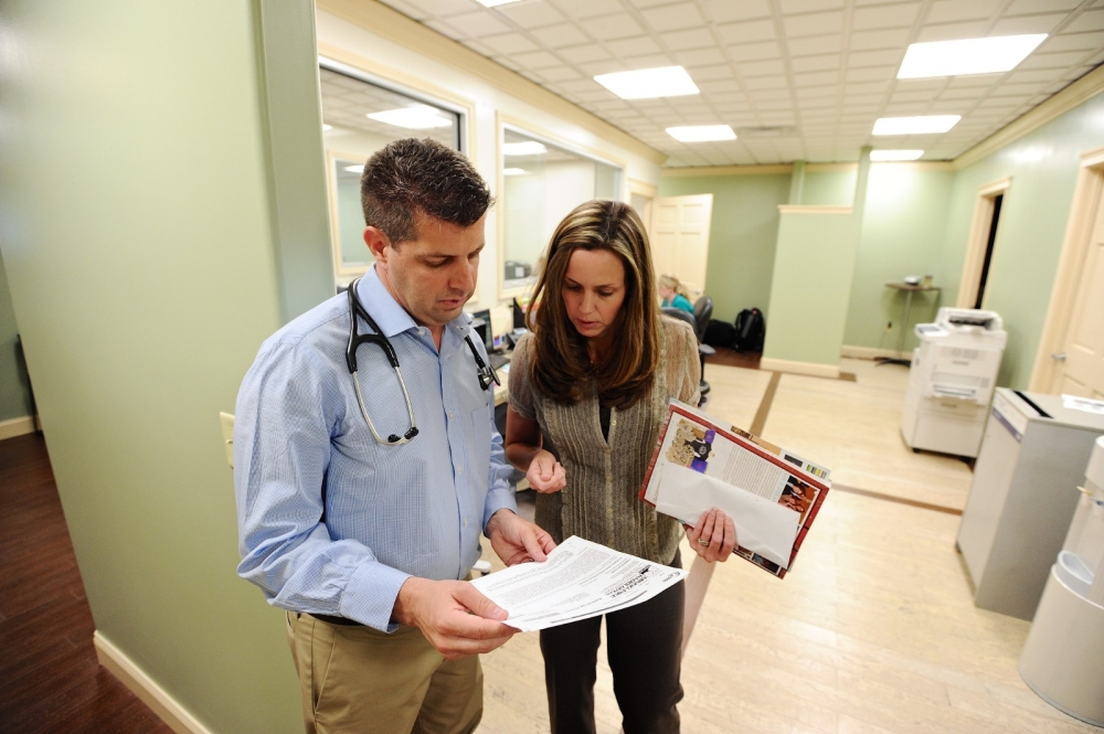 A doctor discusses paperwork with a colleague.