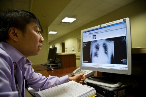 A doctor looks at a patient's digital x-ray.