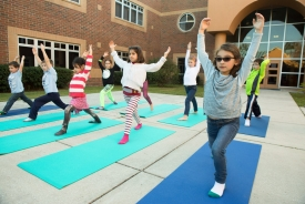 Students doing yoga outside.
