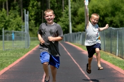 Two boys run on a track.