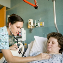 A nurse checks a hospital patient.