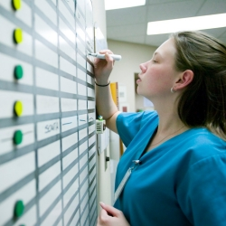 A hospital nurse checking nursing information on a white board.