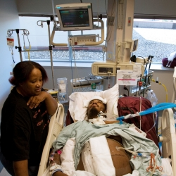 Mother looks over her son as he lies in a hospital recovering from a violent attack.