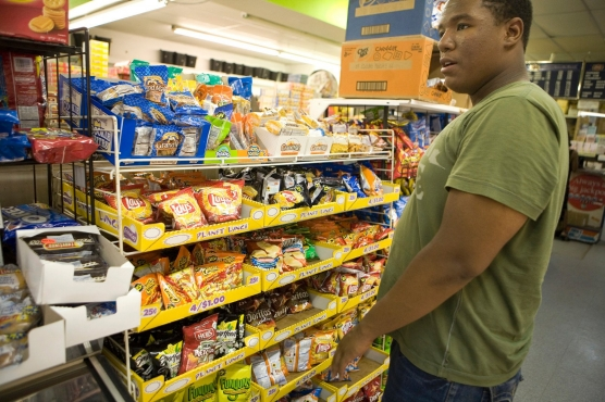 High school student in grocery store looking at snacks options.