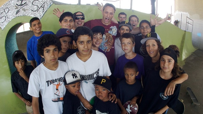 A group of kids ages 6 to 16 stand with Tony Hawk in one of his Foundation's skateparks on San Pedro, California.