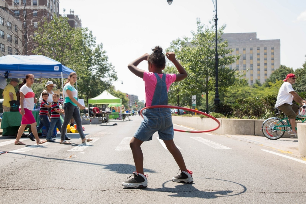 A girl hula hoops in the street during a street festival.
