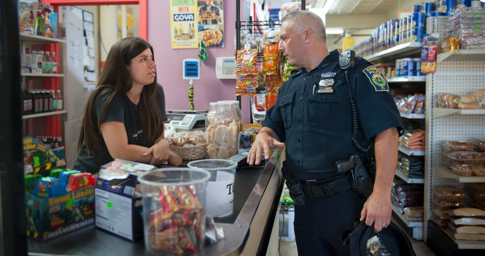 A police officer talks with a cashier while walking his beat.