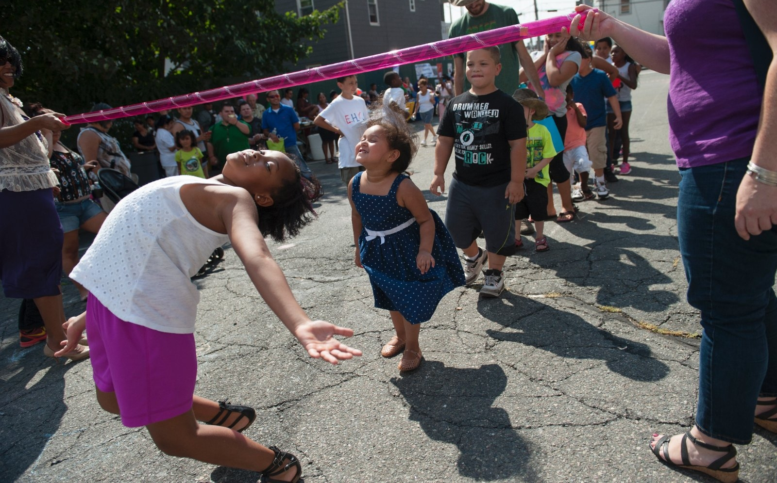 Children participate in the limbo during a block party.