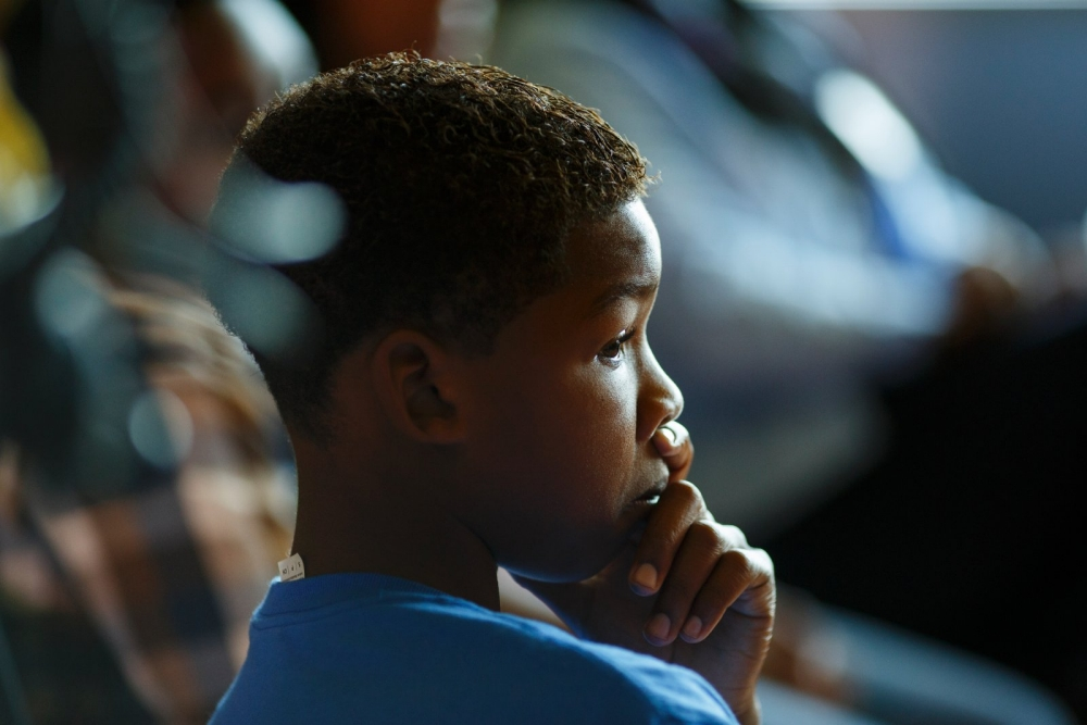 Closeup side profile of a young African American boy listening.
