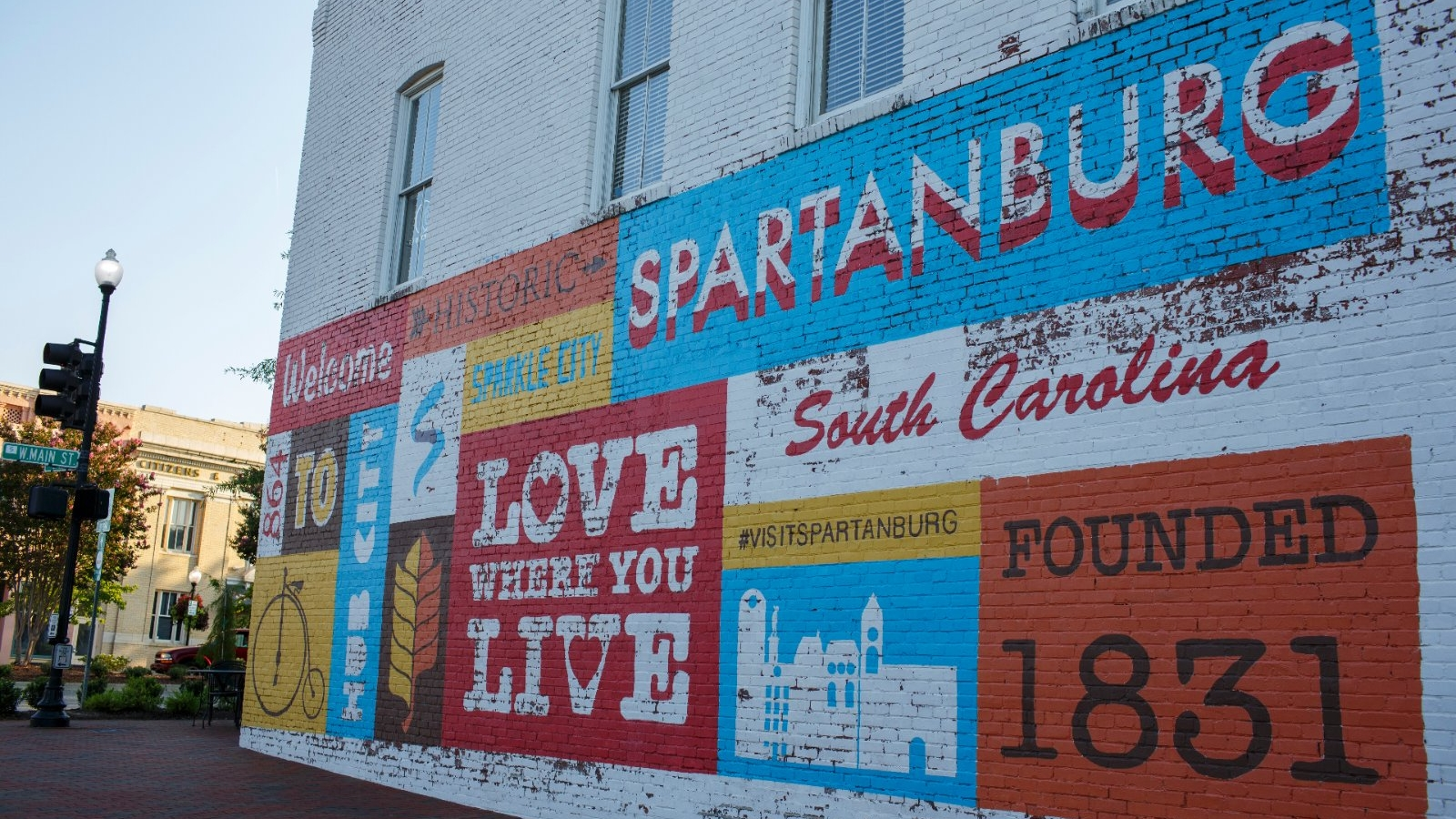 A A mural with a welcoming theme painted on the side of a building in  Morgan Square, Spartanburg, SC.