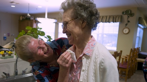 A woman helps an elderly woman at a care facility.