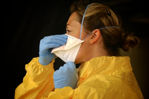 Ebola worker donning protective wear.