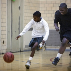 Two boys play basketball in a gym.