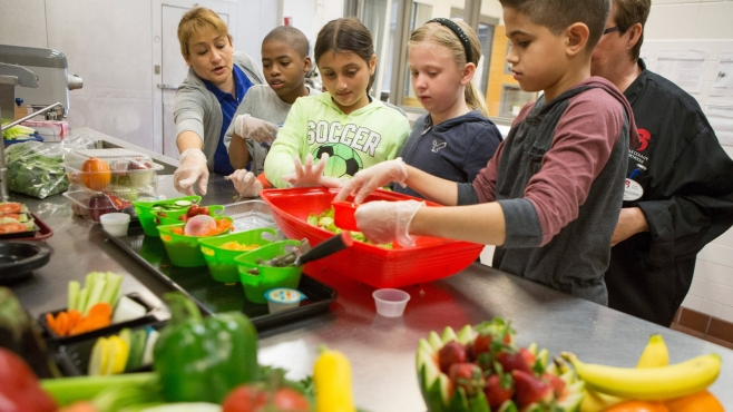 Elementary school students partake in a cooking class.