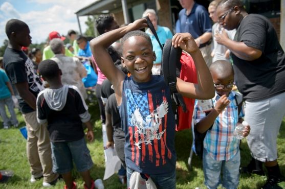 A young boy smiles after receiving a new backpack.