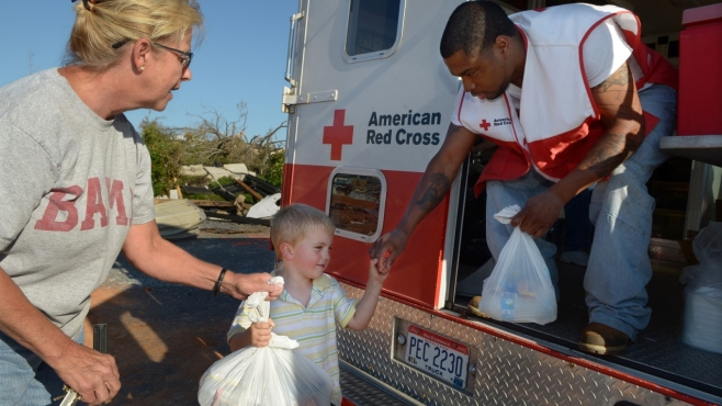 A young boy hands supplies to rescue personnel.