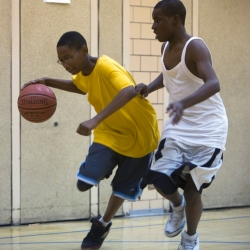 Two boys playing basketball in gym.