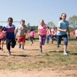 Young children running on a field