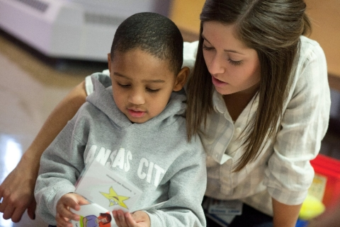 A young woman puts her arm around a preschool boy in a daycare setting.