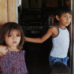 Two young children standing at the door of their trailer.