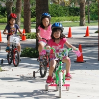 Parent and children ride bikes through the park.