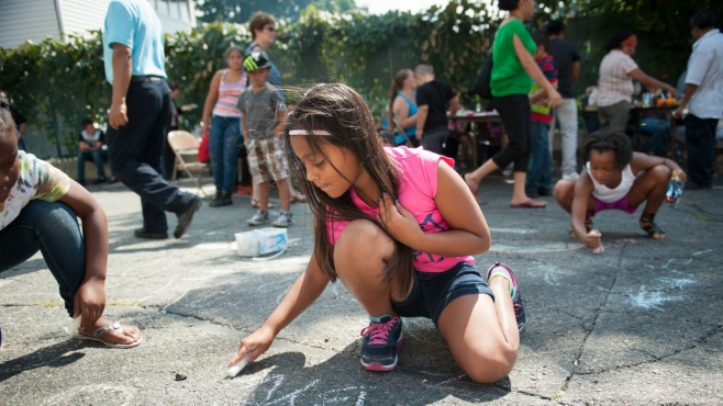 Young girl draws with chalk.