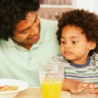 A father and his son eating breakfast cereal and drinking orange juice.