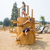 Children climb on a wooden structure at a park.
