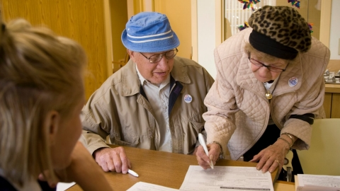 A man and woman sign in at a polling center for flu vaccinations.