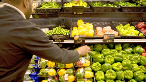 A shopper seleting sweet peppers in a supermarket.