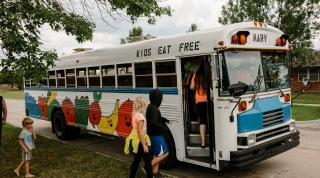 Local youth board a bus in a residential neighborhood.