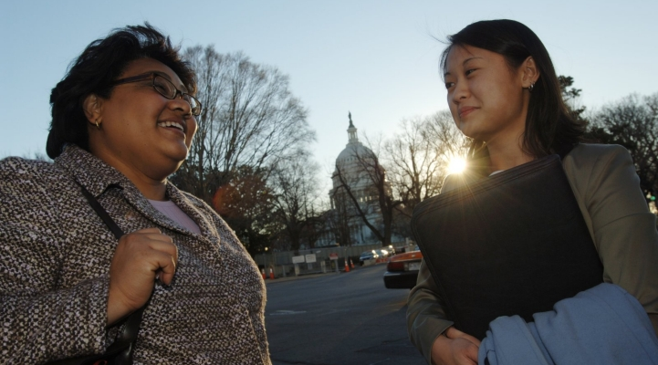 Professional women talk outdoors in Washington, DC, with the Capitol Building in the background.