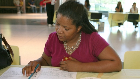 A woman fills out paperwork for health care assistance.