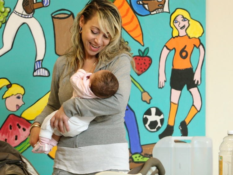 A woman and a baby stand in front of a mural showing children playing.