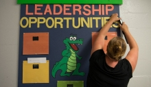 A teacher hangs a sign in an elementary school to promote leadership.