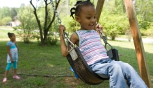 Two girls play on a swing set.