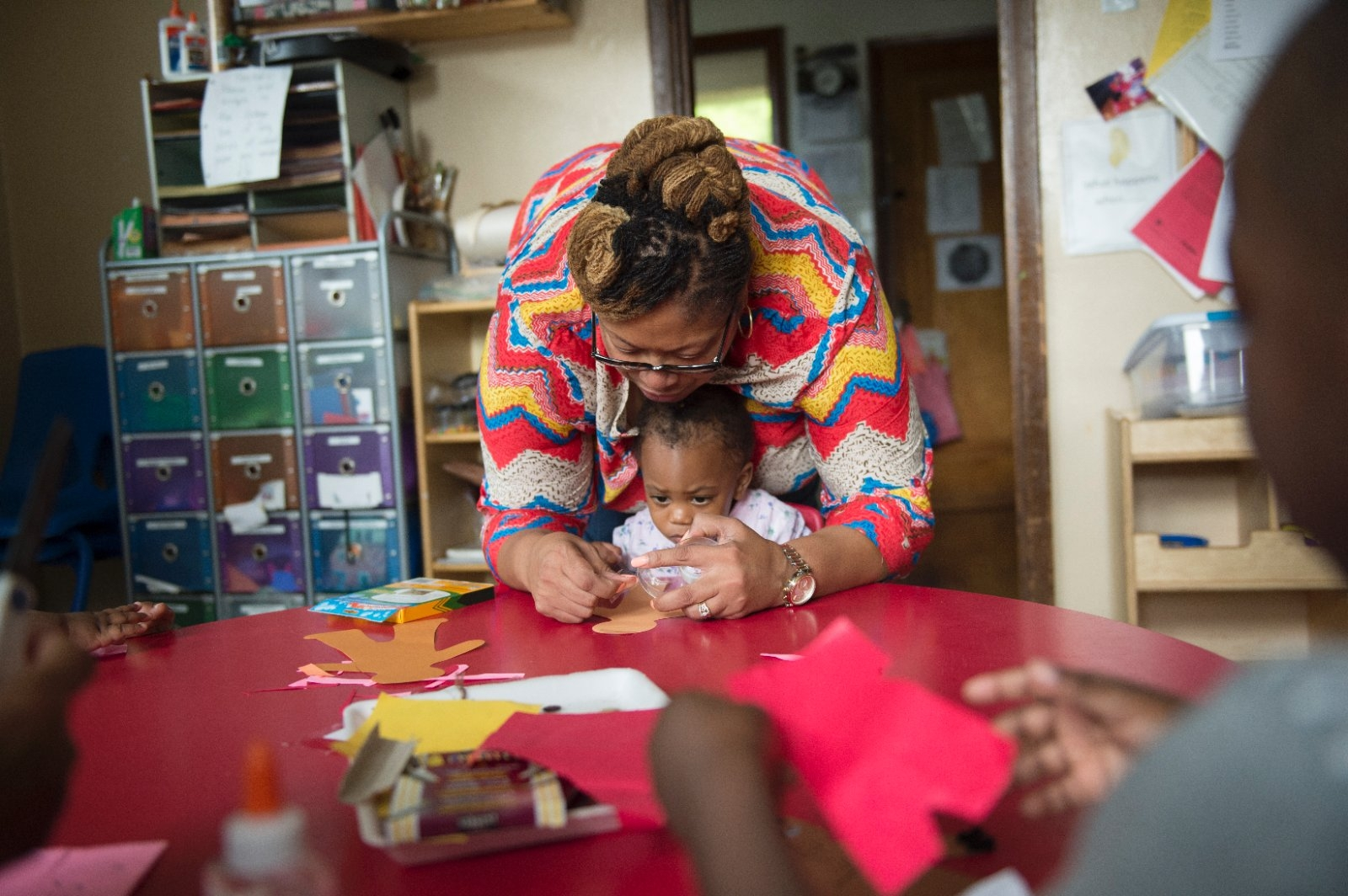 Daycare provider helps a toddler with crafts.