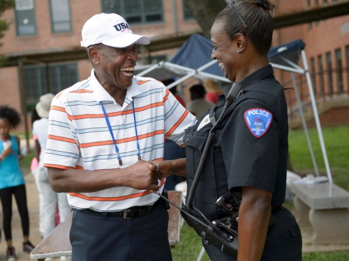 A man shakes hands with a police officer.