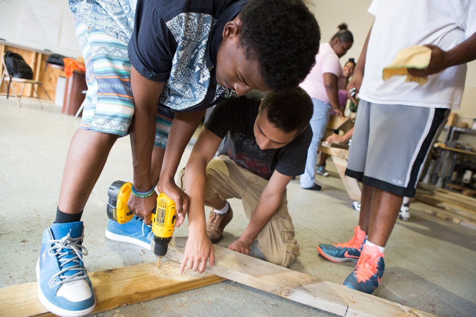 Young adults learn woodworking skills.